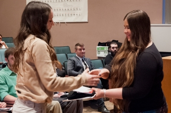 Freshman Anne Zukowski receives her induction materials from SCJ Vice President Autumn Granza. Photo credit: Paul Sevensky