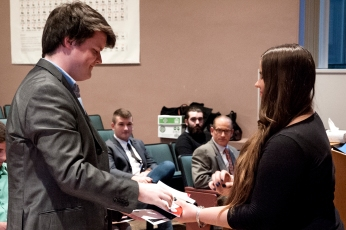 Junior Patrick Kernan receives his initiation materials from SCJ Vice President Autumn Granza. Photo credit: Erica Nealon
